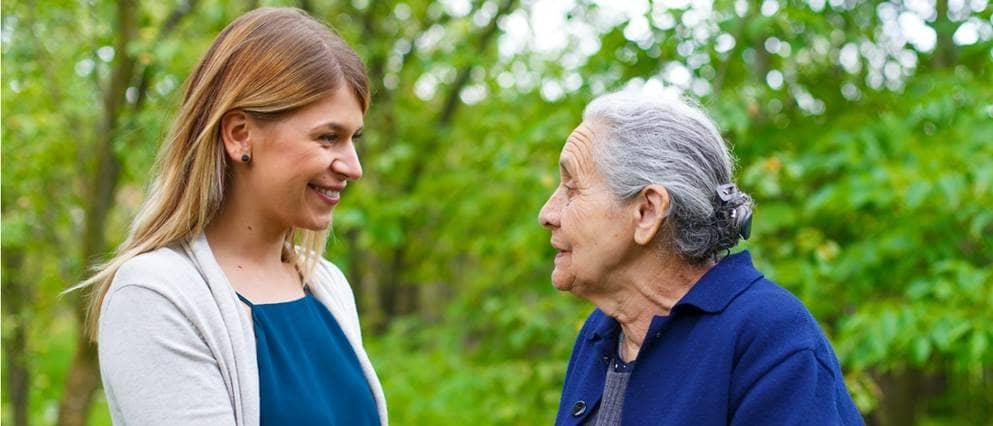 Oudere dame in gesprek met kleindochter in het park