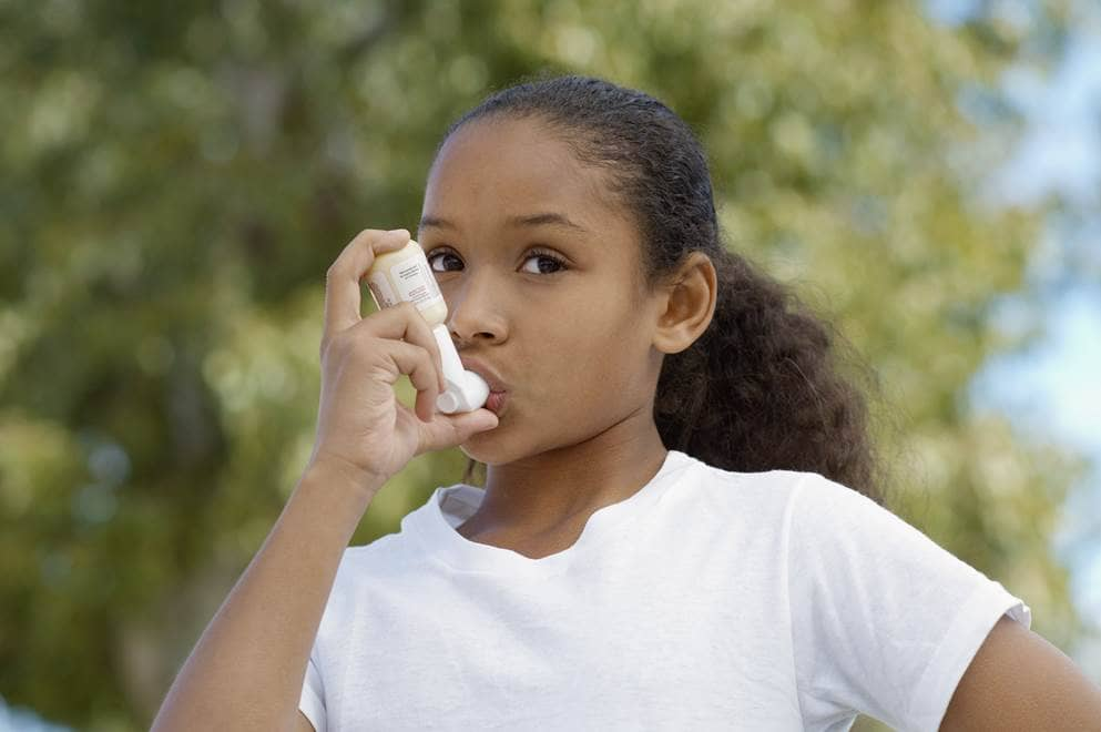 Een meisje gebruikt haar inhalator