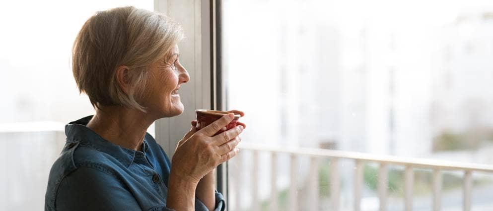 vrouw kijkt uit het raam