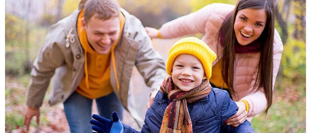 Een gezin speelt lachend in de herfst bladen