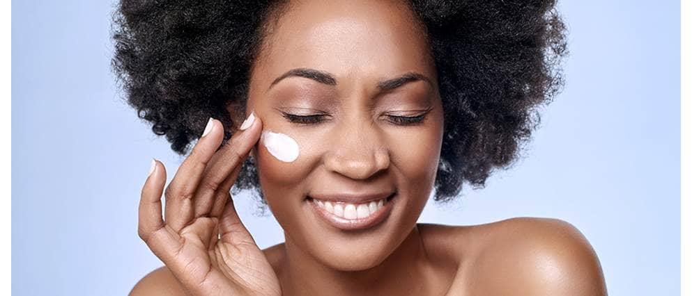 Jonge vrouw smeert dagcrème op haar gezicht
