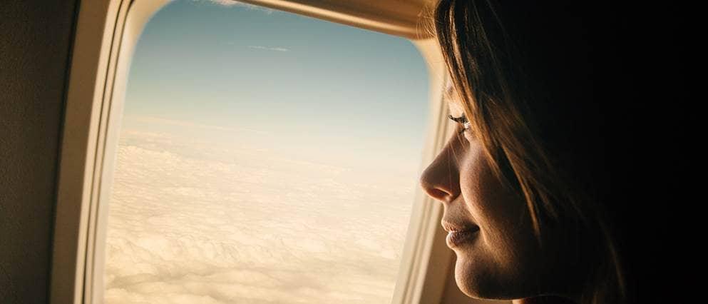 Een vrouw kijkt glimlachend uit het vliegtuigraam